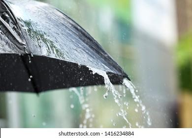 Black umbrella outdoors on rainy day