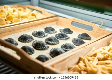 Black Uncooked Ravioli mix on wooden tray in the shop window. Different kind of dry homemade dumpling. Italian foods concept and menu design