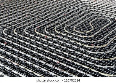 Black underfloor heating posed in a under construction building
