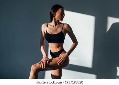 In black underwear. Young caucasian woman with slim body shape is indoors at daytime.