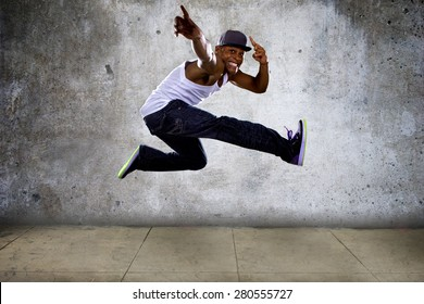 Black urban hip hop dancer jumping high on a concrete background.  The man is doing parkour or leaping.