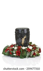Black urn and floral wreath on white background