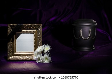 black urn with golden decoration, white chrysanthemum, blank golden mourning frame on deep purple background for sympathy card