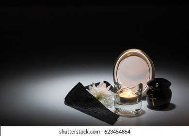 black urn with black tape,white chrysanthemum, candle,for sympathy card on background