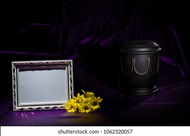 black urn with yellow chrysanthemum and blank horizontal picture frame on deep purple background for obituary card