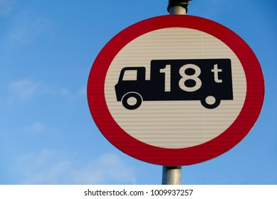 Black van lorry truck on white background in red warning circle with 18t in white. 18 ton tonne maximum load. Road safety sign isolated on blue sky background