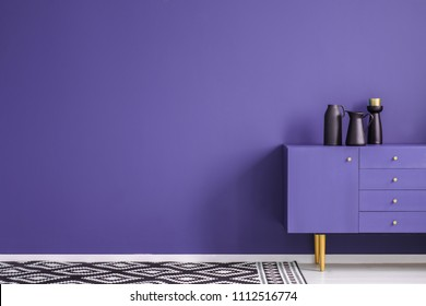 Black vase on violet cabinet against the wall with copy space in minimal living room interior with carpet