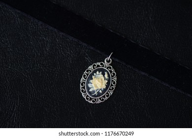 Black velvet choker necklace with rose cameo pendant on a dark background close up