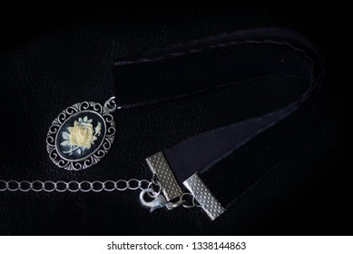 Black velvet choker with rose cameo on a dark background close up