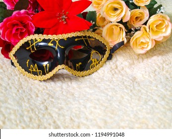 Black Venetian Mask with gold decorations, in the background colorful flowers, on wool.