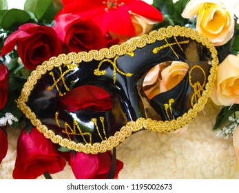 Black Venetian Mask with gold decorations, on colorful roses, in the background cream colored wool.