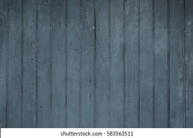 Black vertical faded worn weathered vertical wooden bead boards or wainscotting type planks.