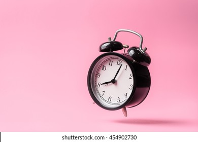 black vintage alarm clock falling on the floor with color background