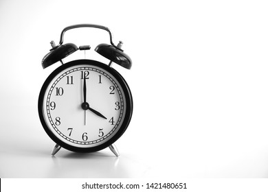 Black vintage alarm clock on table. White background. An image of a retro clock showing 04:00 pm/am.