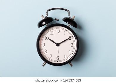 Black vintage alarm clock on blue background. Time concept