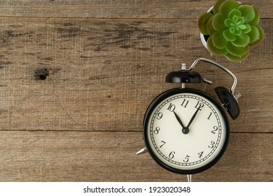 Black vintage alarm clock on a shabby wooden board background. Copy space. Flat lay.