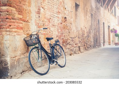 Black vintage bicycle left on a street in Pienza in Tuscany, Italy
