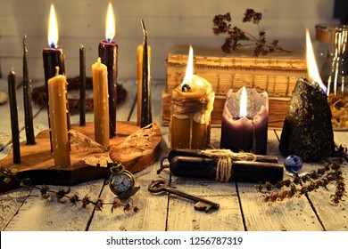 Black and vintage candles with key and vintage clock on old table planks. Magic ritual. Wicca, esoteric and occult background with vintage witch objects