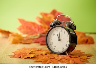 Black vintage clock with dried maple leaves on green background