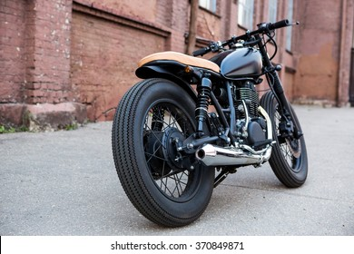 Black vintage custom motorbike motorcycle caferacer in front of brick wall. Back view.