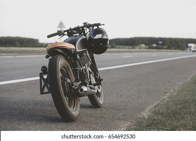 Black vintage custom motorcycle motorbike caferacer standing on the road during sunset