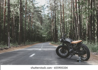 Black vintage custom motorcycle motorbike caferacer standing in the forest road during sunset