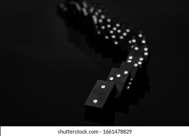 Black vintage falling dominoes on a black background, selective focus. WB photo.
