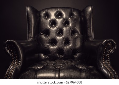 Black vintage leather armchair boss on a black background with w