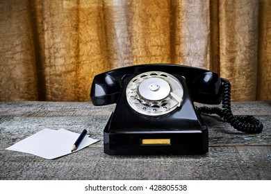 Black vintage phone on wooden background with pencil close-up, pick up the phone
