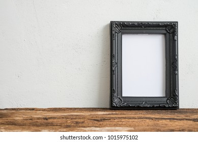 Black vintage photo frame on old wooden table over white wall background