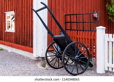 Black vintage pull cart standing outside a red and white wooden house on a gravel path.