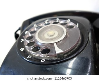 A black vintage rotary dial phone with a circular dialing wheel