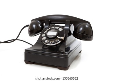 A black vintage rotary phone on a white background