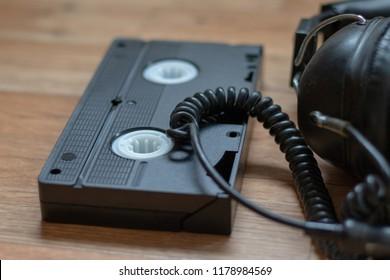 Black vintage videocassette beside old headphones on a wooden table