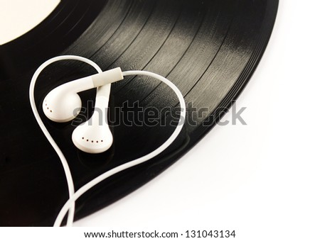 Black vintage vinyl record with  white modern  headphones isolated on white. Love music