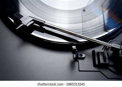 Black vinyl record spinning on a turntable - close up of a tonearm , lp and turn table