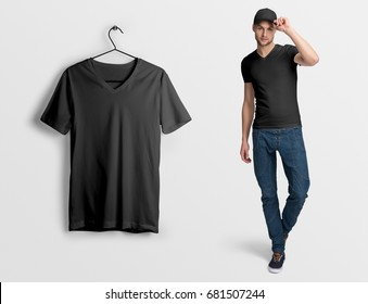 Black v-neck t-shirt on a man in jeans and baseball cap, isolated, mockup. Hanging blank v-neck t-shirt, against empty wall.