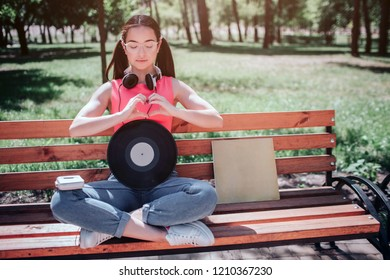 Black vynil is leaning to woman`s body. There is a music player on her knee. She is keeping her eyes closed.