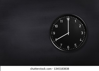 Black wall clock showing eight o'clock on black chalkboard background. Office clock showing 8am or 8pm on black texture