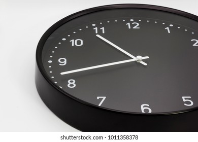 Black Wall clock with white numbers closeup on white background. Include path for selection, dicut work.