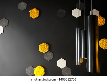 Black wall with decorative orange and yellow honey cell of moss and loft creative lamp. In interior of cafe . Loft space design creative minimalistic cafe concept, black and yellow colors.Creative spa