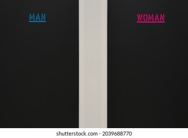 A black wall divided by a pipe with blue and pink text MAN and WOMAN  , concept of opposite sex and gender,  difference between male and female leads to different attitude expectations or perceptions