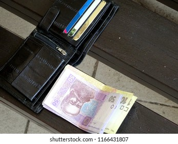 Black wallet with credit cards and cash money of Ukraine (hryvnia, grivna)