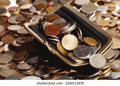 Black wallet with different coins. Big heap of shiny coins as background.