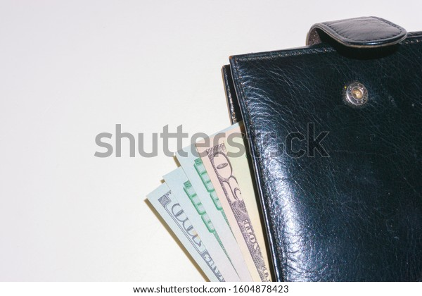 Black wallet with dollars deployed horizontally. Top view of a new black genuine leather wallet with banknotes isolated on a white background. Flat lay with copy space. Prosperity symbol.