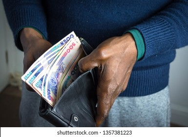 Black wallet with naira notes of five hundred naira denomination in Nigerian businessman hand for personal finance and money concept