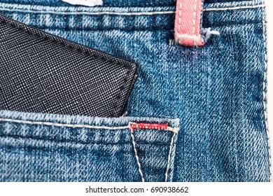 Black wallet on blue jean pocket