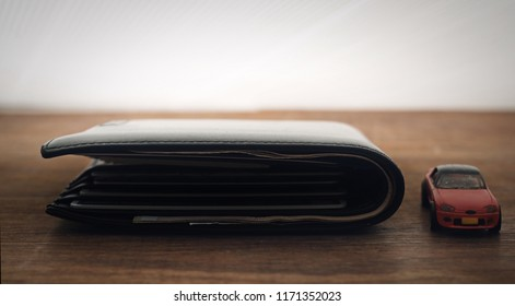 black wallet with plastic car model on wooden table, finance concept