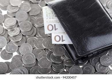 Black wallet with ten polish zloty paper money laying on one polish zloty coins. Money and savings concept.