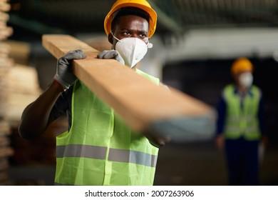 Black warehouse worker wearing protective face mask while working at lumberyard during coronavirus pandemic.